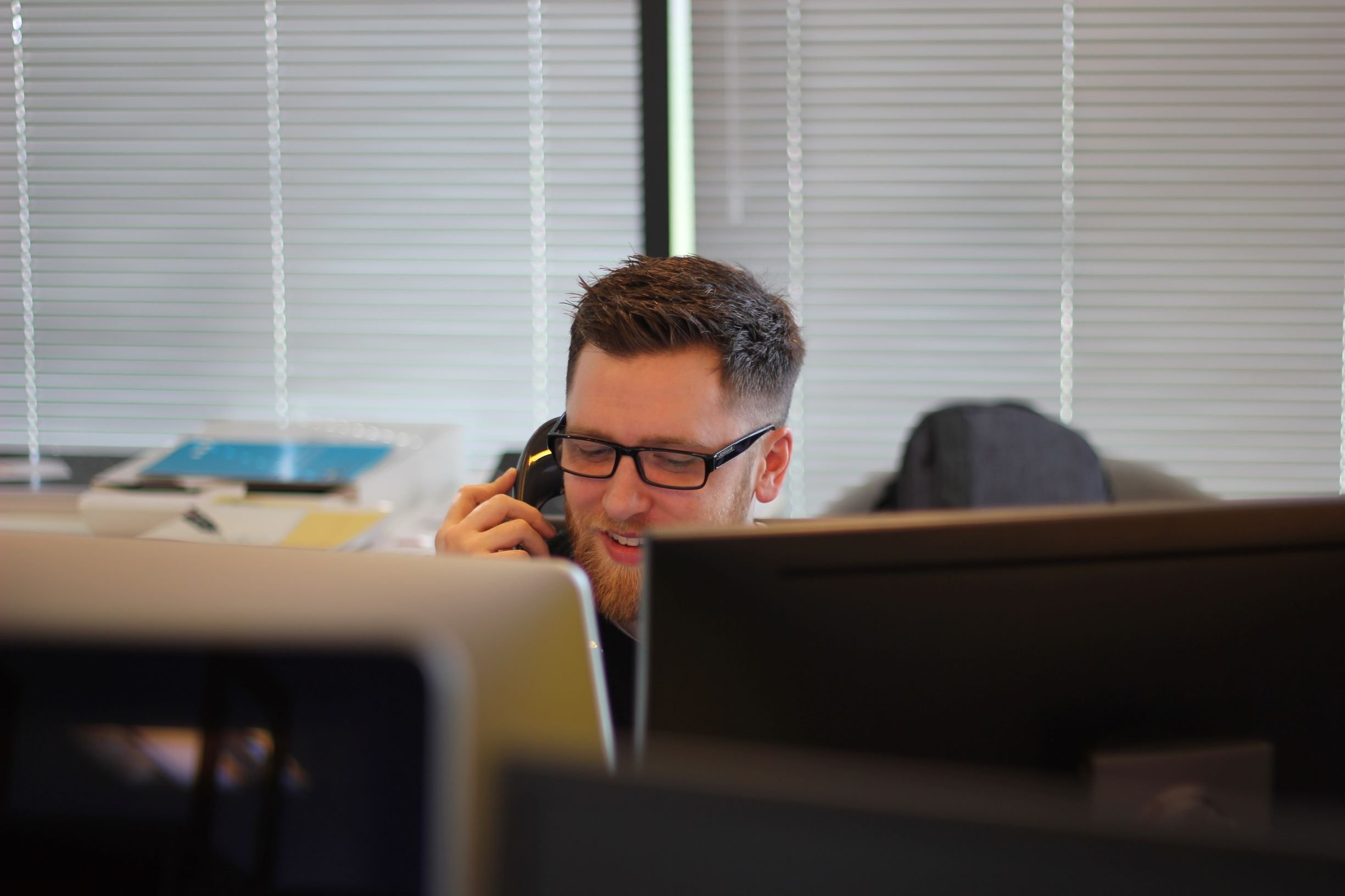 Man answers a question on the phone in front of computer monitors