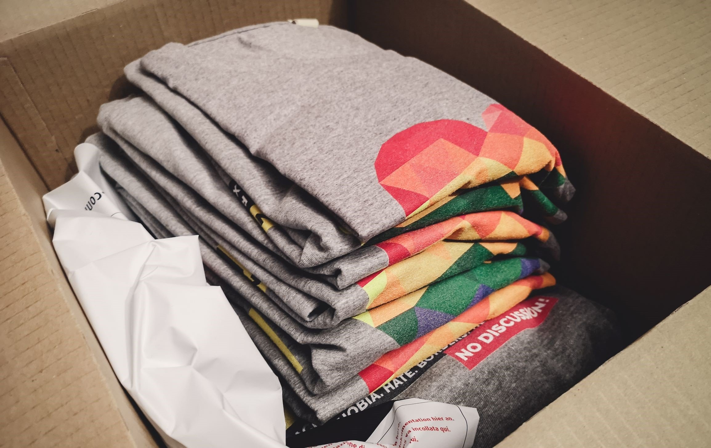 A stack of rainbow print t-shirts in a shipment box, ready for delivery