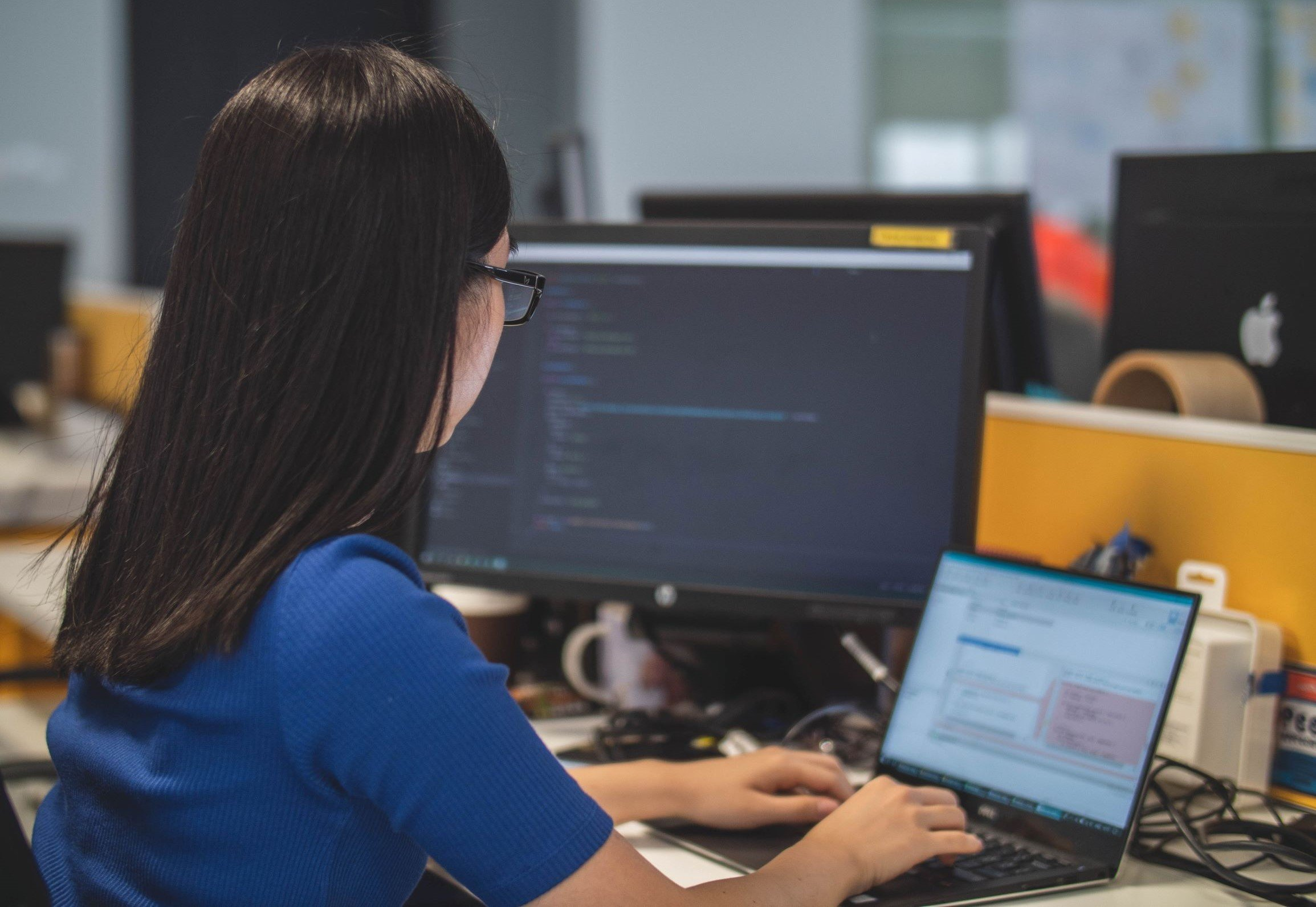 Woman coding on laptop and monitor, building a website